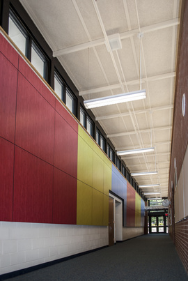 The mixture of primary red, blue, and yellow colored panels in the hallway of Ogden Elementary School break up the space and create a stimulating effect for children.